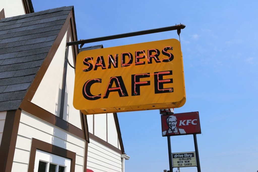 Comparing early signage from Sander's original fried chicken cafe and it's franchised spin-off: Kentucky Fried Chicken/