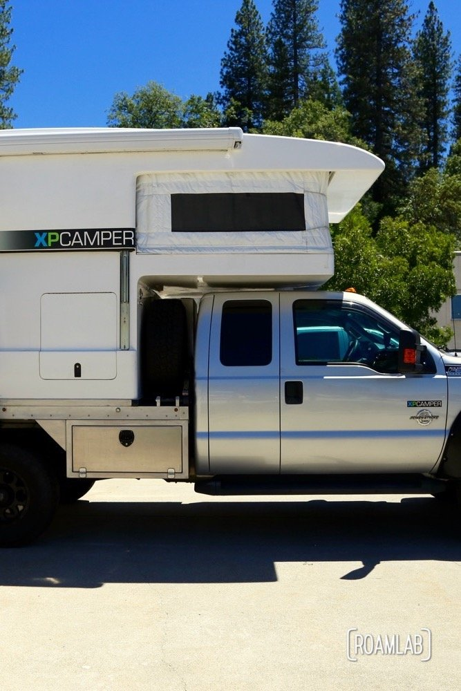 This is a fully expanded XP Camper. The section above the truck cab is fabric but everything else has hard siding. You can see a line along the center of the body where the top section slides over the bottom section when the camper is compressed. The side entrance allows a full width table with picture window at the back but means that this camper is not a slide in. The truck bed is converted to allow a full width camper. See the industrial metal base that is substituted for a truck bed.