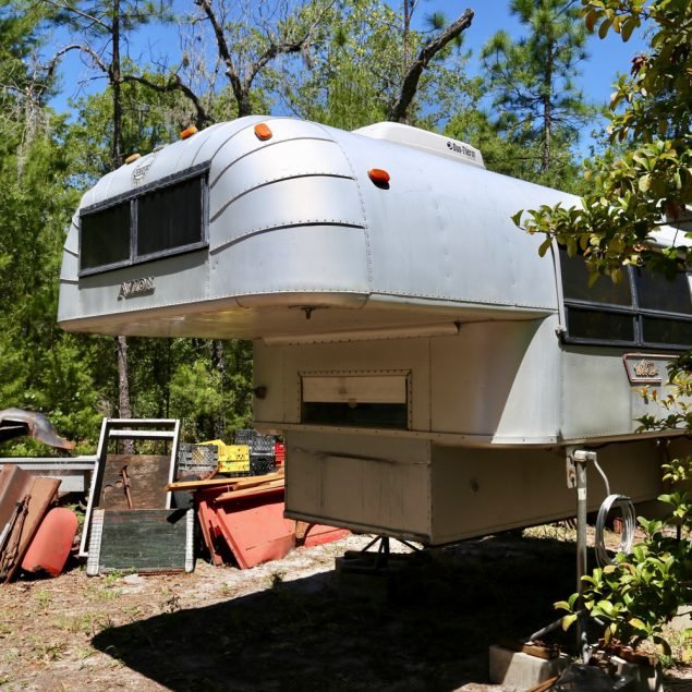 1970 Avion C11 truck camper floating on jacks in the back yard of its previous owner.