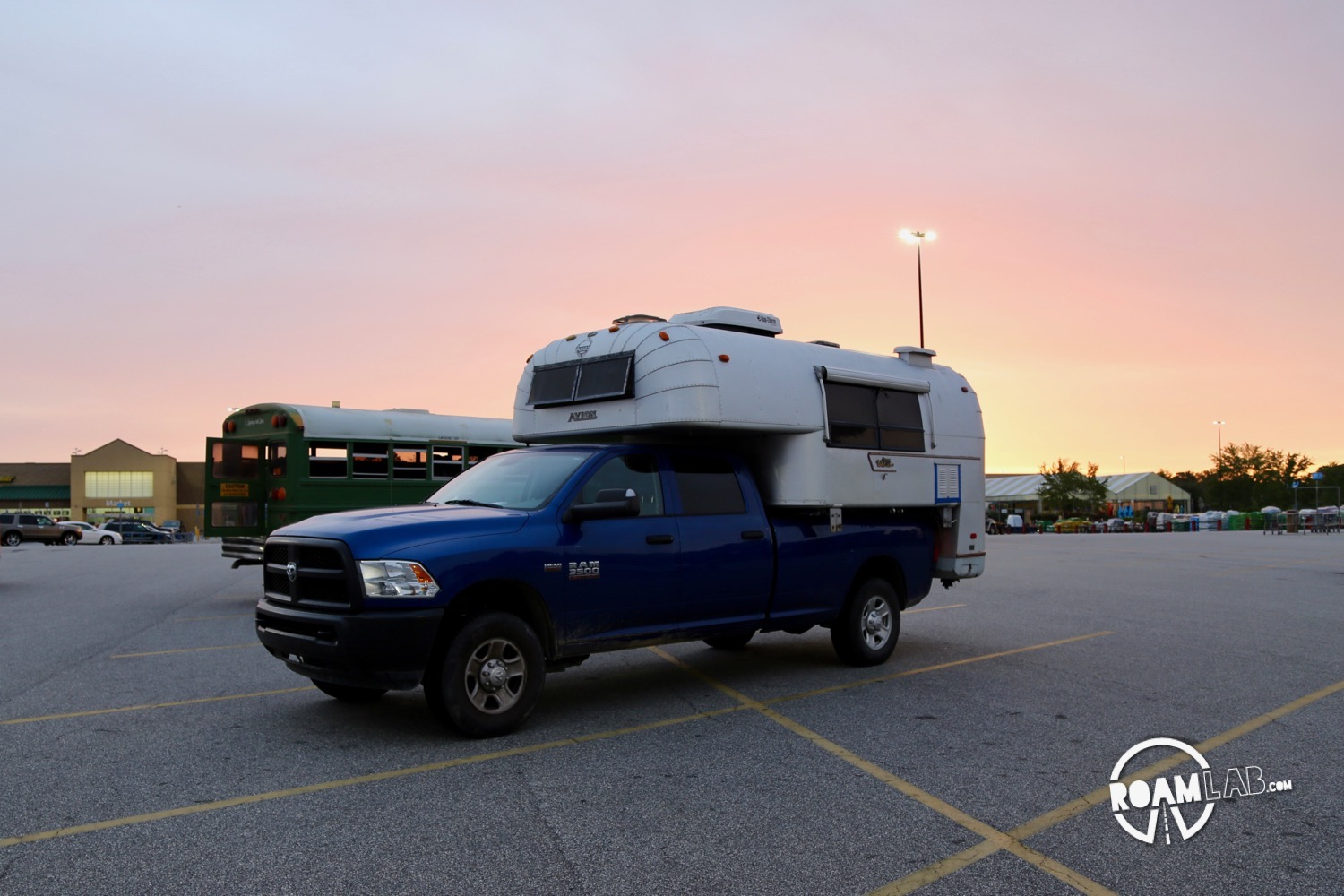 Sun setting over a 1970 Avion C11 truck camper parked in a Walmart Parking lot.