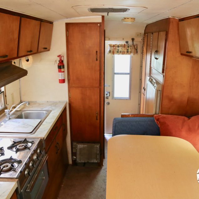 Interior view of a 1970 Avion C11 truck camper featuring a kitchen counter top, dinette table, stove, sink, refrigerator, overhead storage, and exit door.