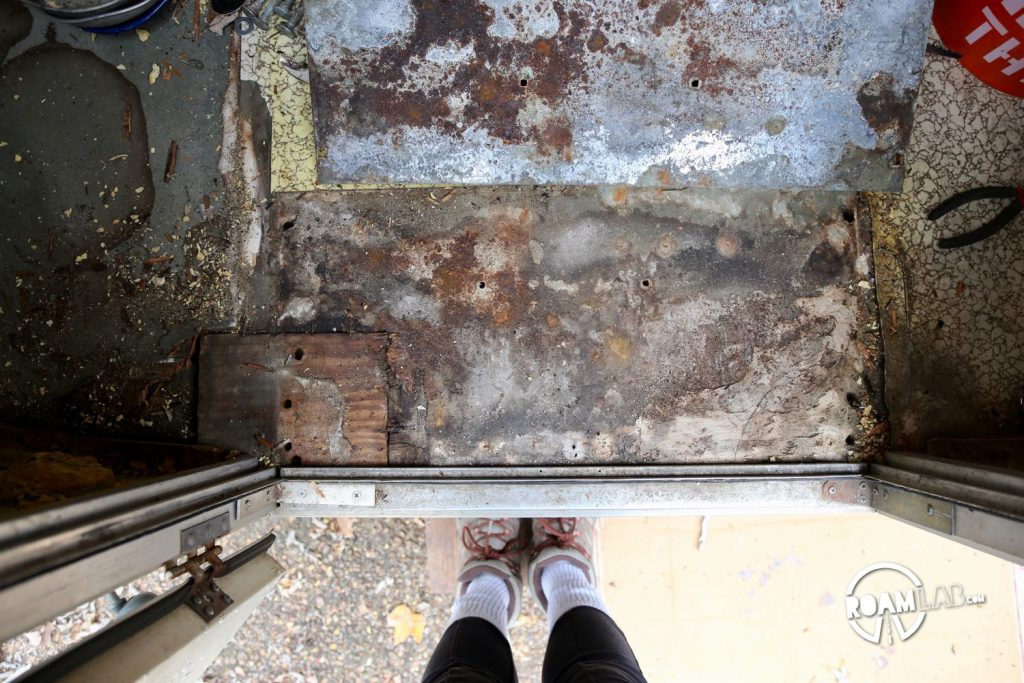 This section of the original entry shows previous efforts the patch and strengthen the rotting floor including the block of wood on the lower left and some kind of hardened putty material on the lower right.