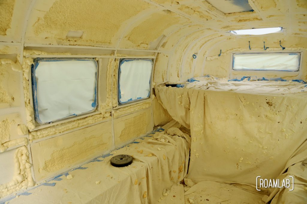 Truck camper interior covered with drop clothes, plastic sheet, and masking tape after painting.