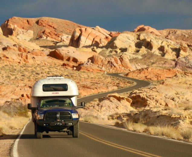 1970 Avion C11 truck camper driving down Mouses Tank Road in Valley of Fire State Park, Nevada.