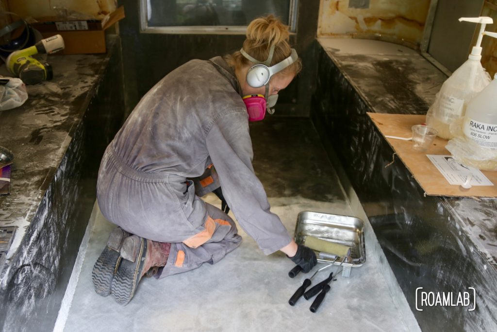 Rolling out air bubbles from fiberglass cloth to re-enforcing the truck camper floor.