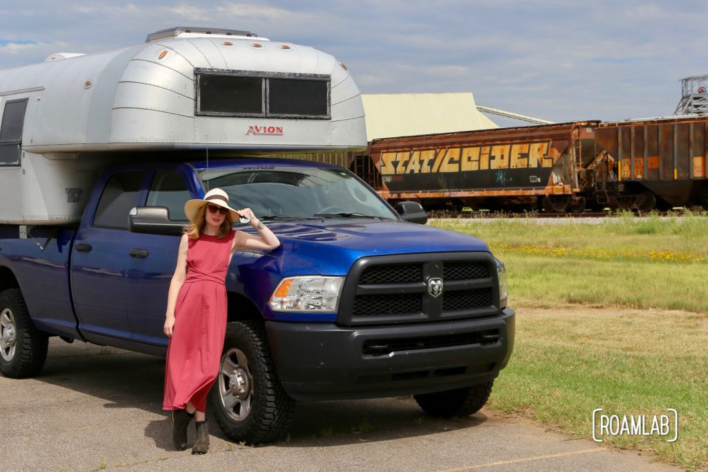 Woman next to a 1970 Avion C11 truck camper by the train tracks