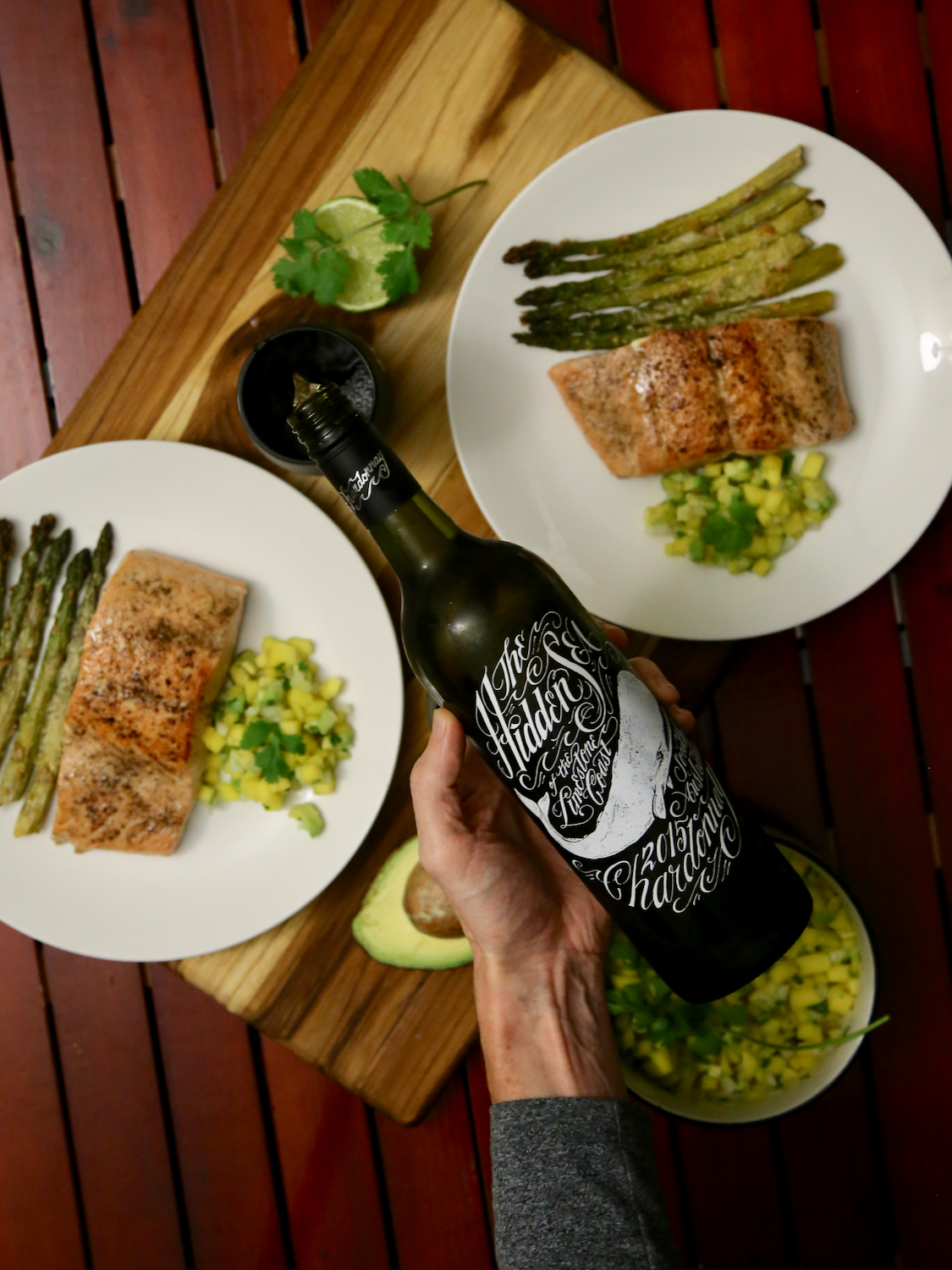 Hand pouring a bottle of wine with a salmon dinner