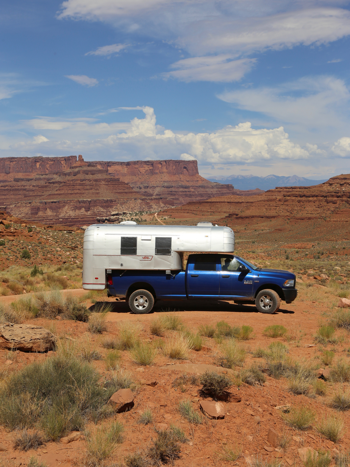 Aluminum truck camper on a blue truck on a dirt road in the middle of Canyonlands National Park