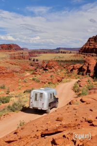 Aluminum Avion C11 truck camper driving down Shafer Road through Canyonlands National Park.
