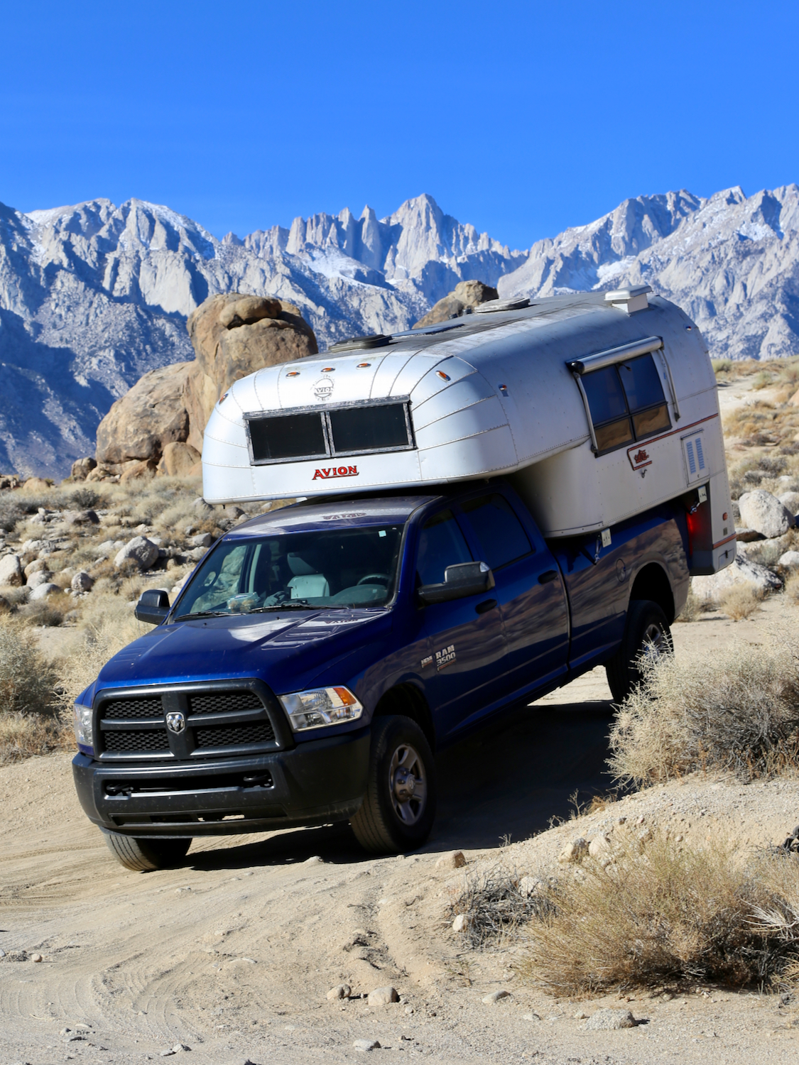 Aluminum truck camper on a blue truck exploring the Eastern Sierras of California