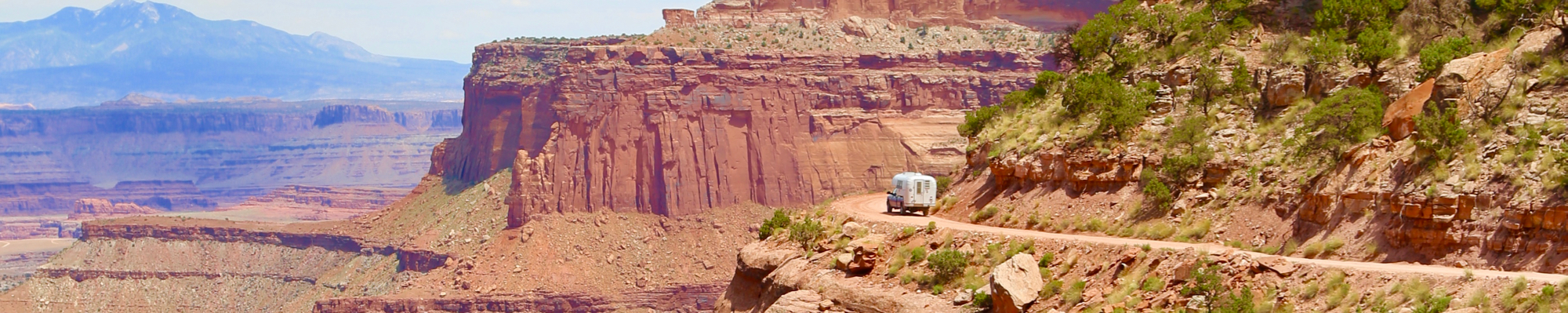 1970 Avion C11 truck camper traveling down Shafer Trail in Canyonlands National Park.