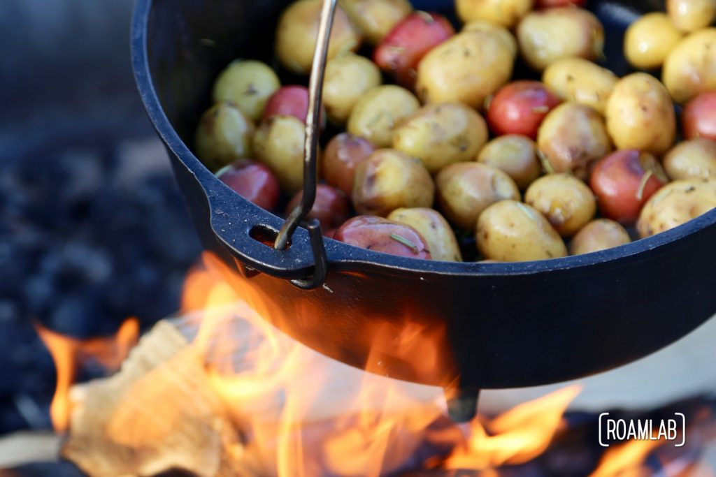 Cooking colorful potatoes in a cast iron dutch oven over a campfire