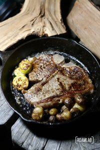 Porterhouse ready to eat with yellow squash and roasted potatoes.