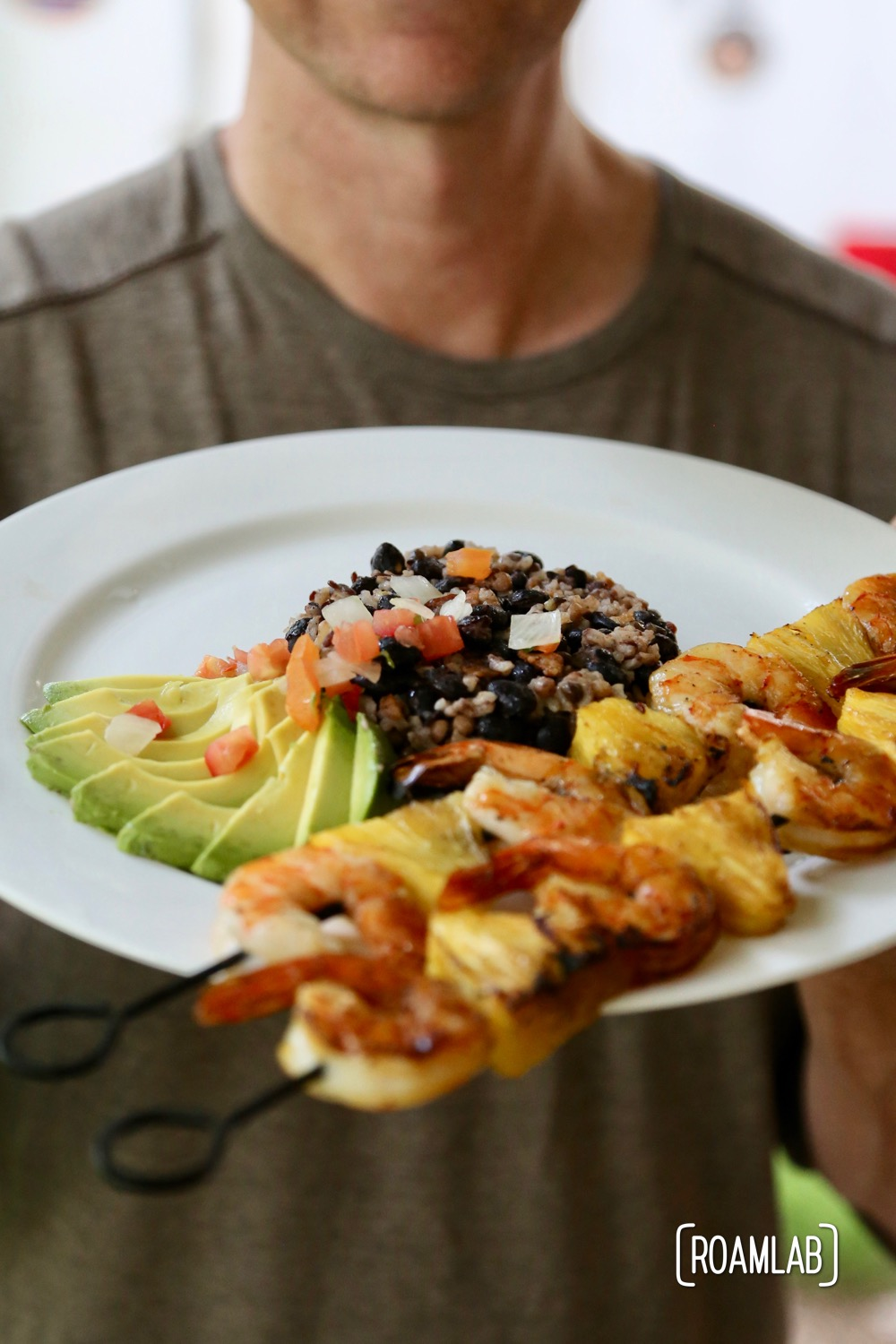 Pineapple shrimp skewers with avocado, beans, rice, and pico de gallo.