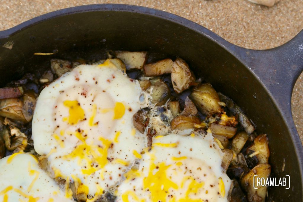 Cast iron skillet bacon and eggs hash on the beach.