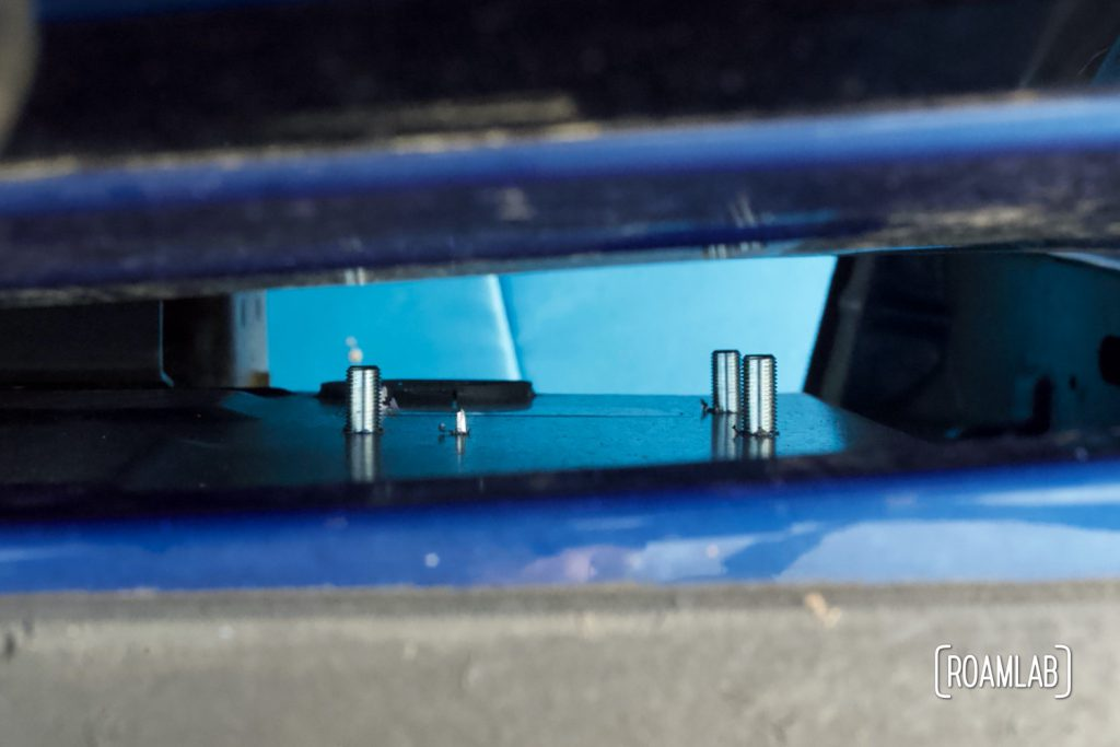 Four bolts sticking through guide plate inside the truck bed, ready to secure the front anchor mount.