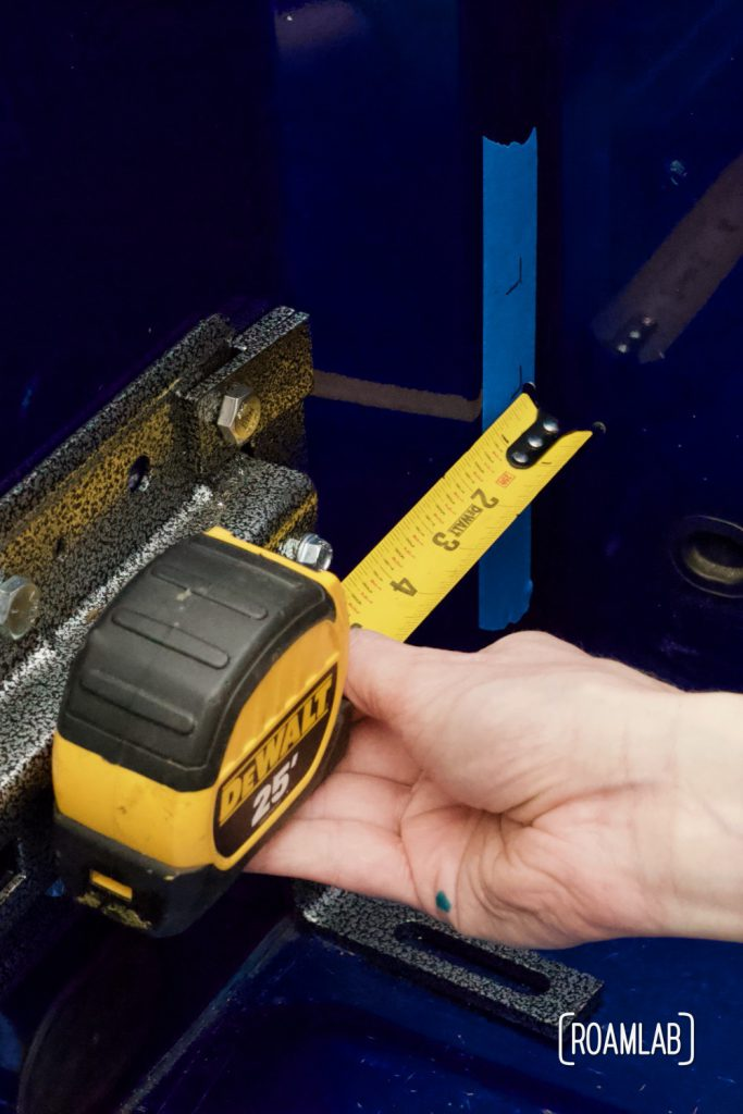 Measuring from the guide plate to determine where to drill pilot holes to secure the backing plate on the other side.