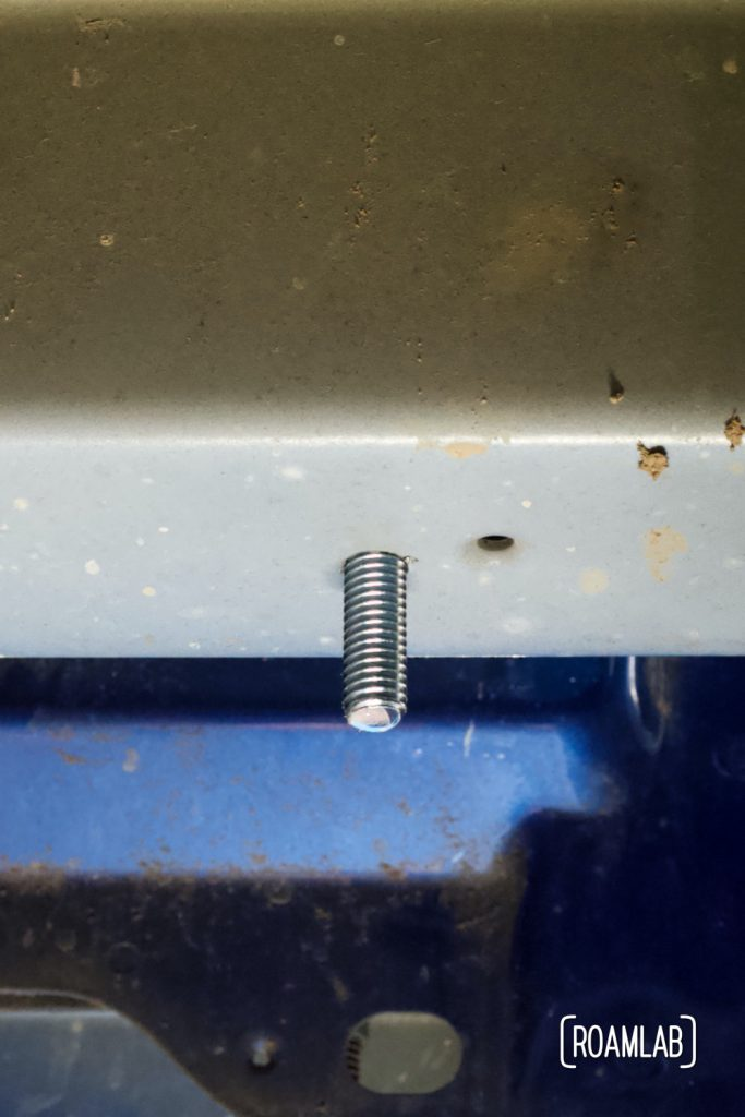 Bolt in place through frame brace as seen from under the truck bed.  The grey bar is part of the truck frame.