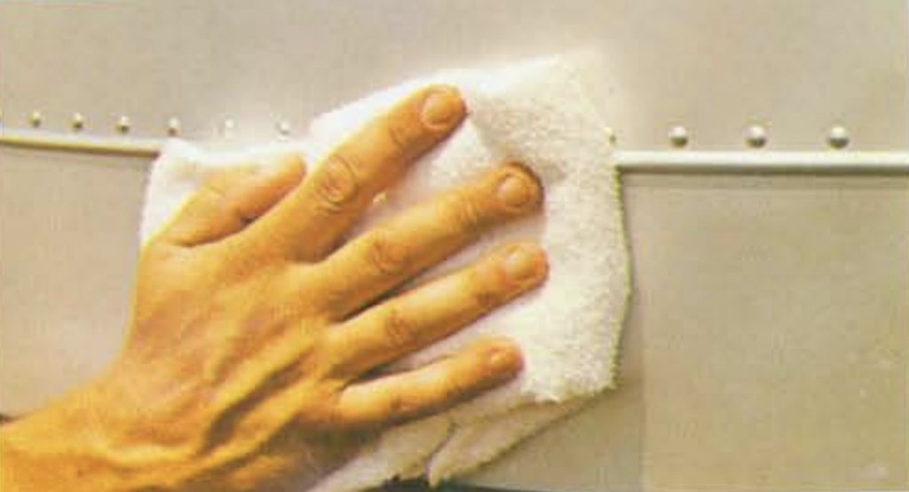 Hand wiping down the riveted exterior of an Avion travel trailer.