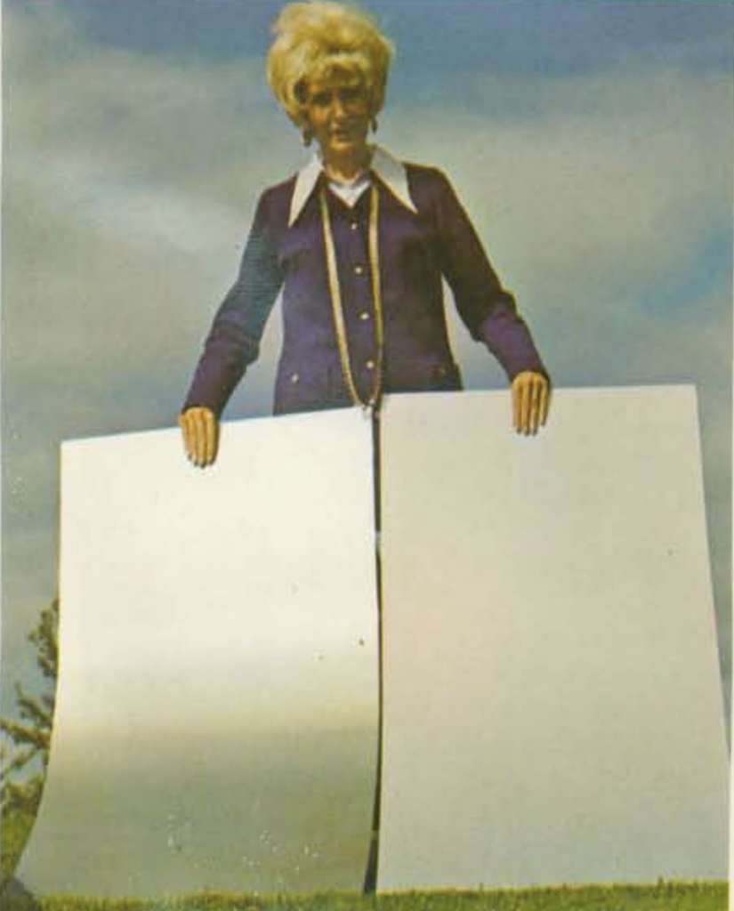 Woman holding up samples of standard aluminum sheet and anodized aluminum sheet.