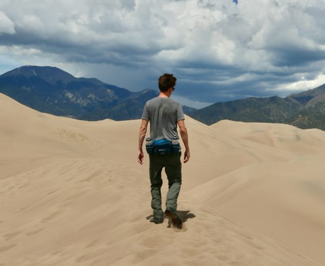 Man hiking to the mountains in the Great Sand Dunes National Park