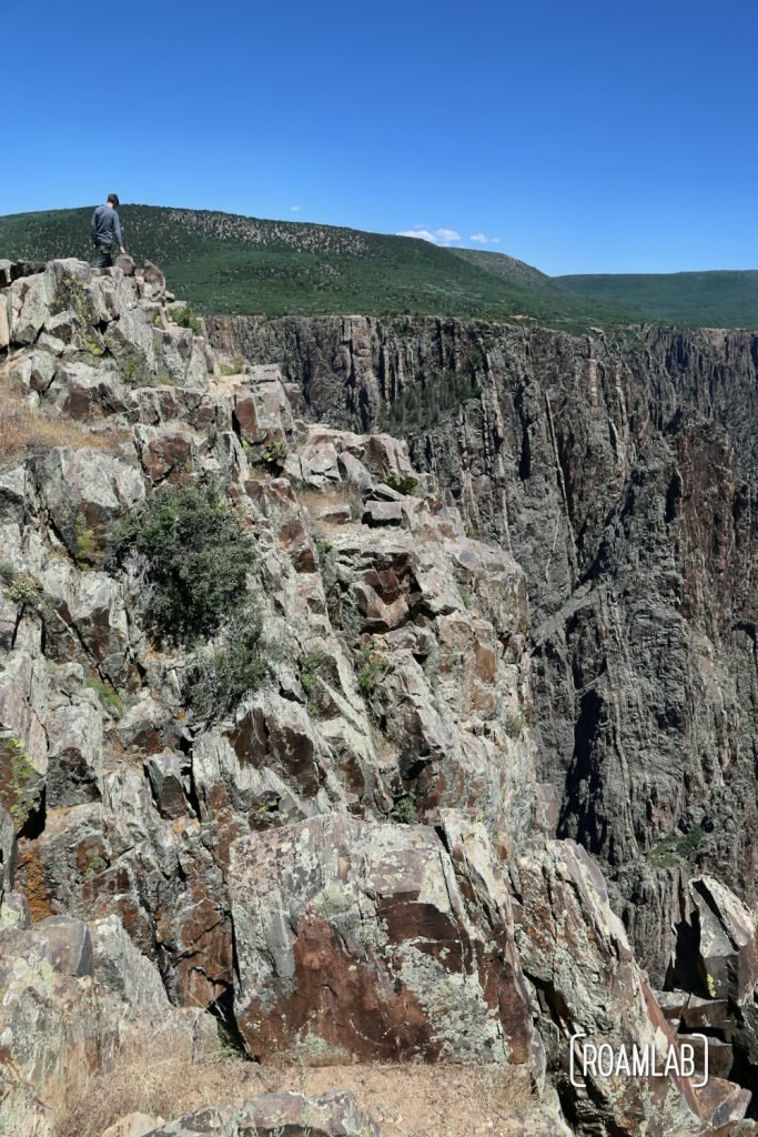 Chris standing at the top of a cliff looking down into the Black Canyon of the Gunnison National Park in Colorado
