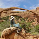 Woman in front of Landscape Arch in the Devil's Garden of Arches National Park, Utah.