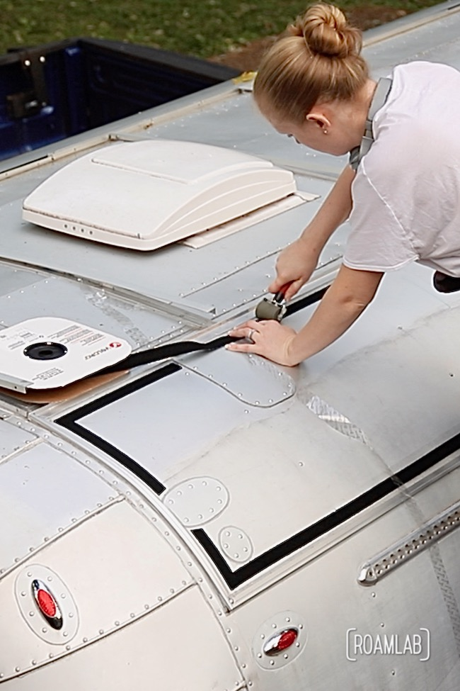 Woman applying velcro to aluminum truck camper roof.