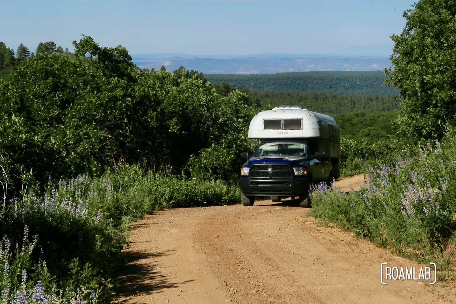 Vintage 1970 Avion C11 truck camper driving down a dirt road on the Rimrocker off-road and OHV trail.