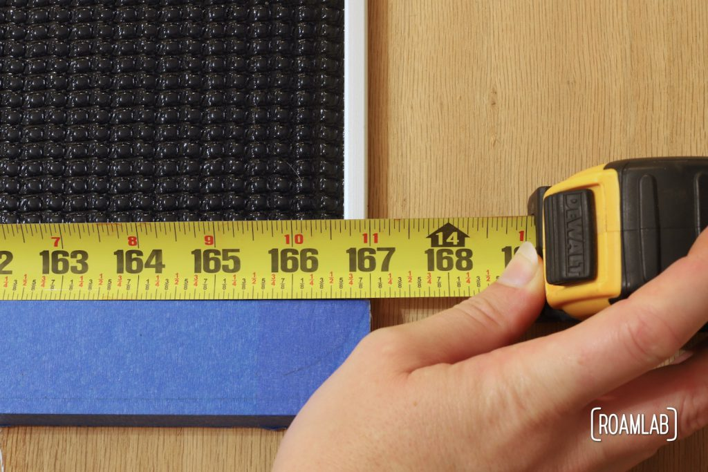 Measuring tape held up against a solar panel indicating a 167-inch distance.