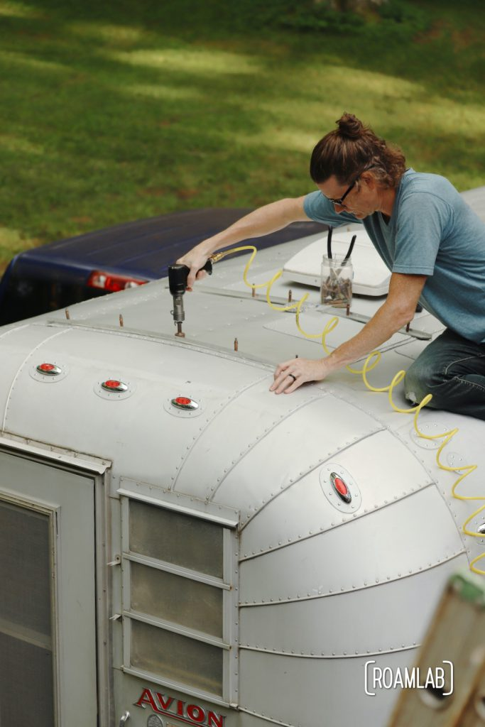Man on roof of vintage 1970 Avion C11 truck camper riveting a piece of aluminum.