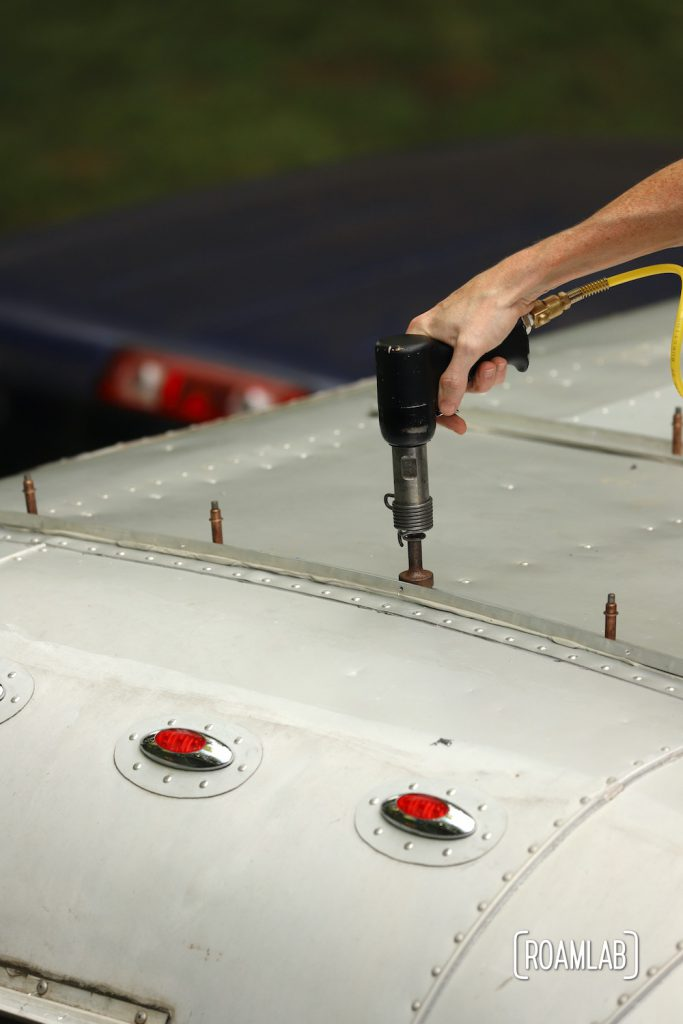 Hand holding a rivet gun to the roof of the aluminum 1970 Avion C11 truck camper.