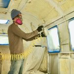 Man applying white paint inside a camper with a spray gun attached to an air compressor.