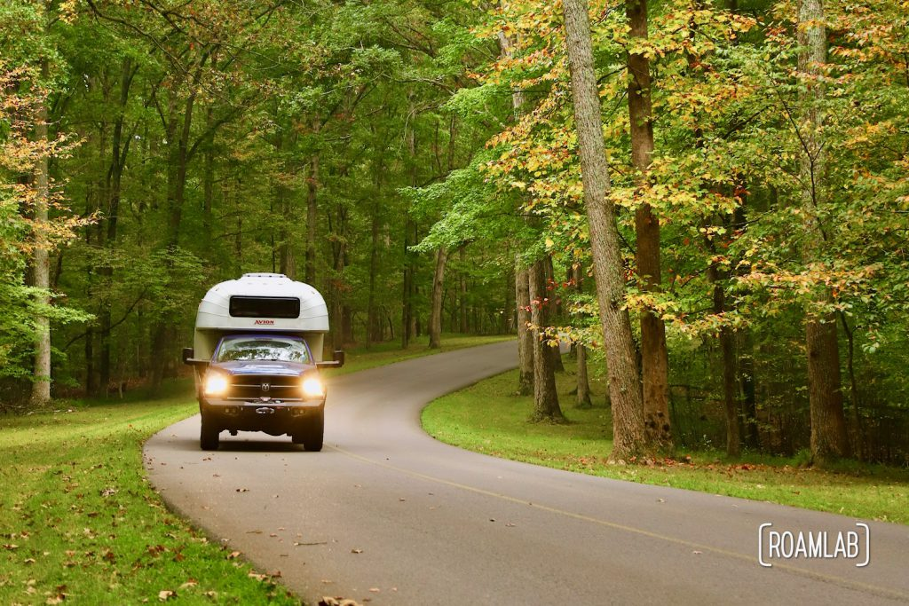 1970 Avion C11 truck camper driving the scenic roads of Montgomery Bell Tennessee State Park in Fall.