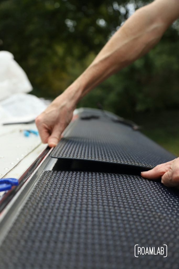 Carefully placing panels on truck camper roof and securing with velcro.