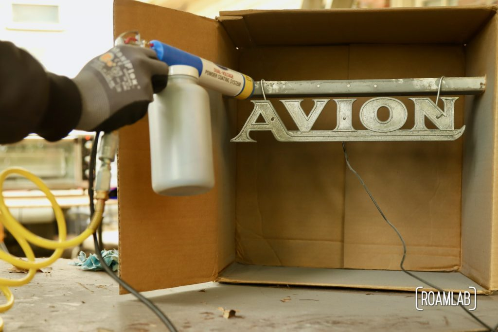 Avion emblem hooked up to the powder coating gun assembly, ready for application.