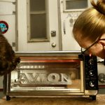 Man and woman watching an Avion emblem with a chrome powder coat cure in a toaster oven.