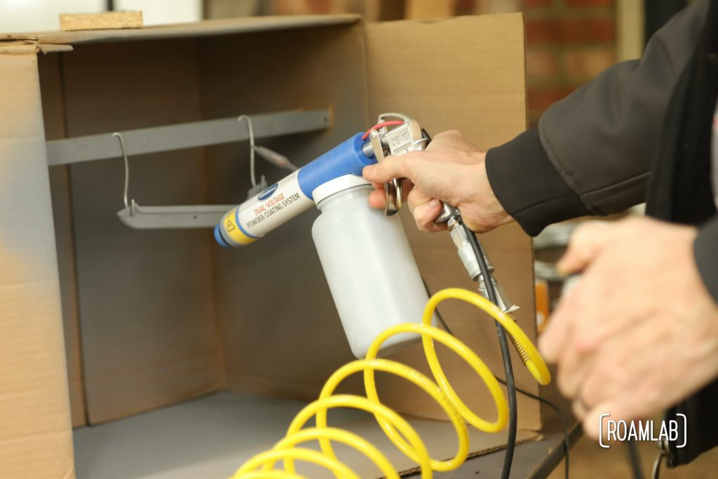 Closeup of hands holding a powder coating gun to apply on an emblem in the backgroun