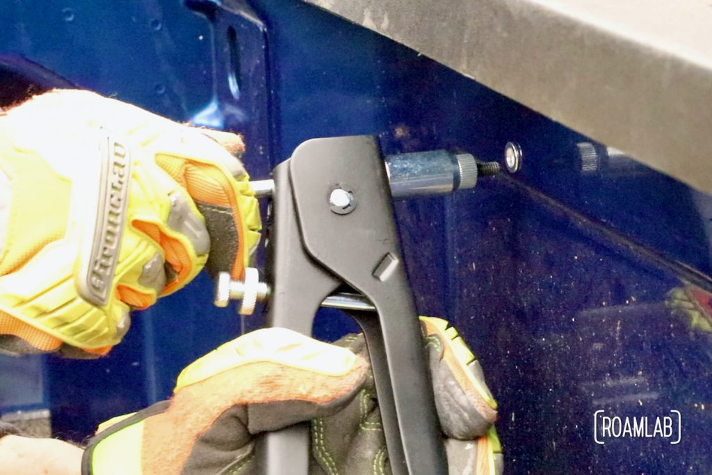 Using a rivet gun to install a rivet nut into the side of a blue truck bed.