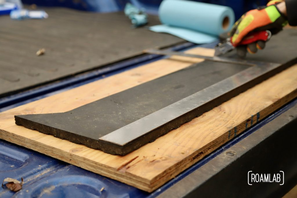 Using a right angle to measure and cut a thick piece of black rubber.