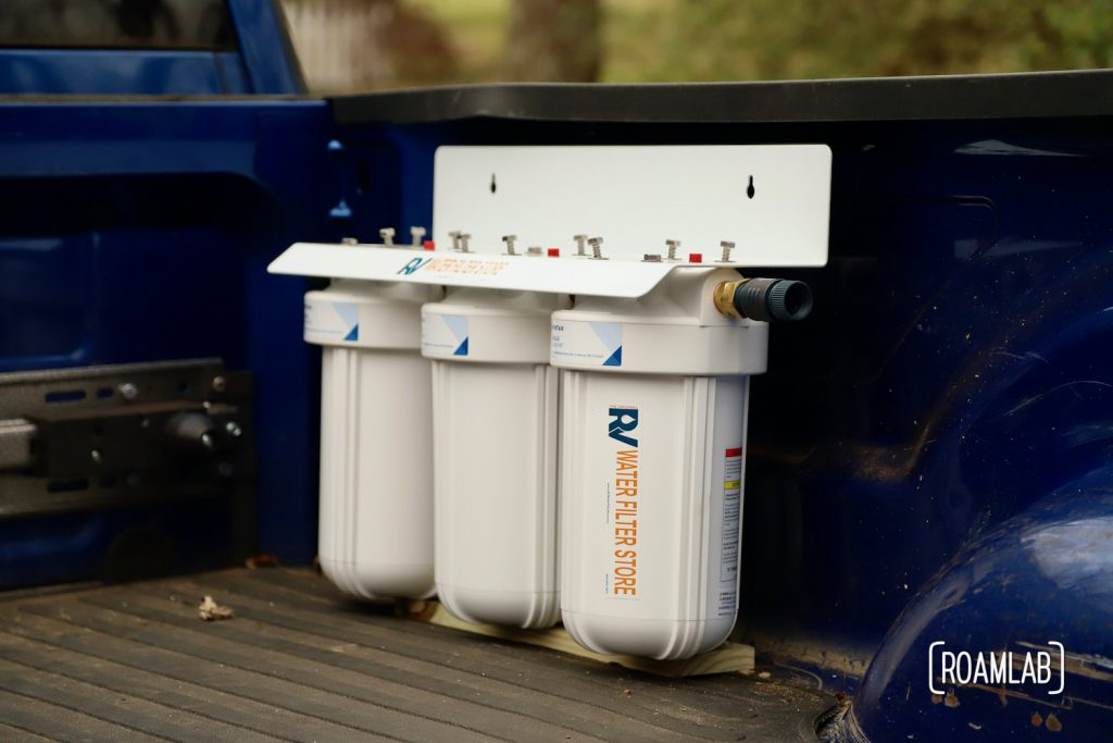 A three container water filter system propped in place on a board of wood inside a truck bed.