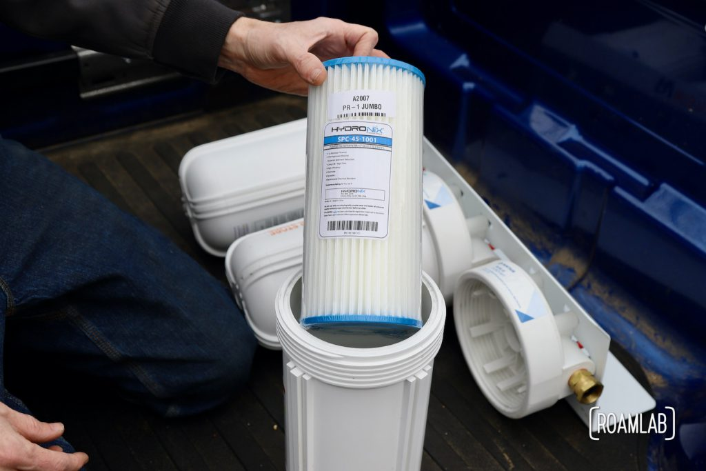 Hand holding a pleated polyester filter before placing it in the canister of a three part water filtration system.