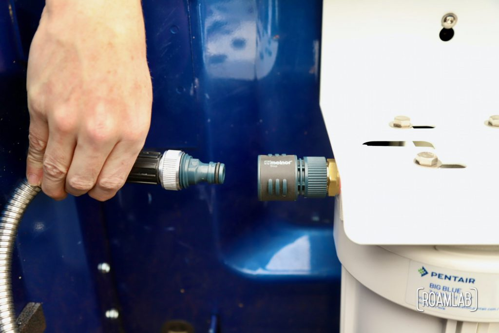 Hand inserting a quick connect hose attachment to a water filtration system.