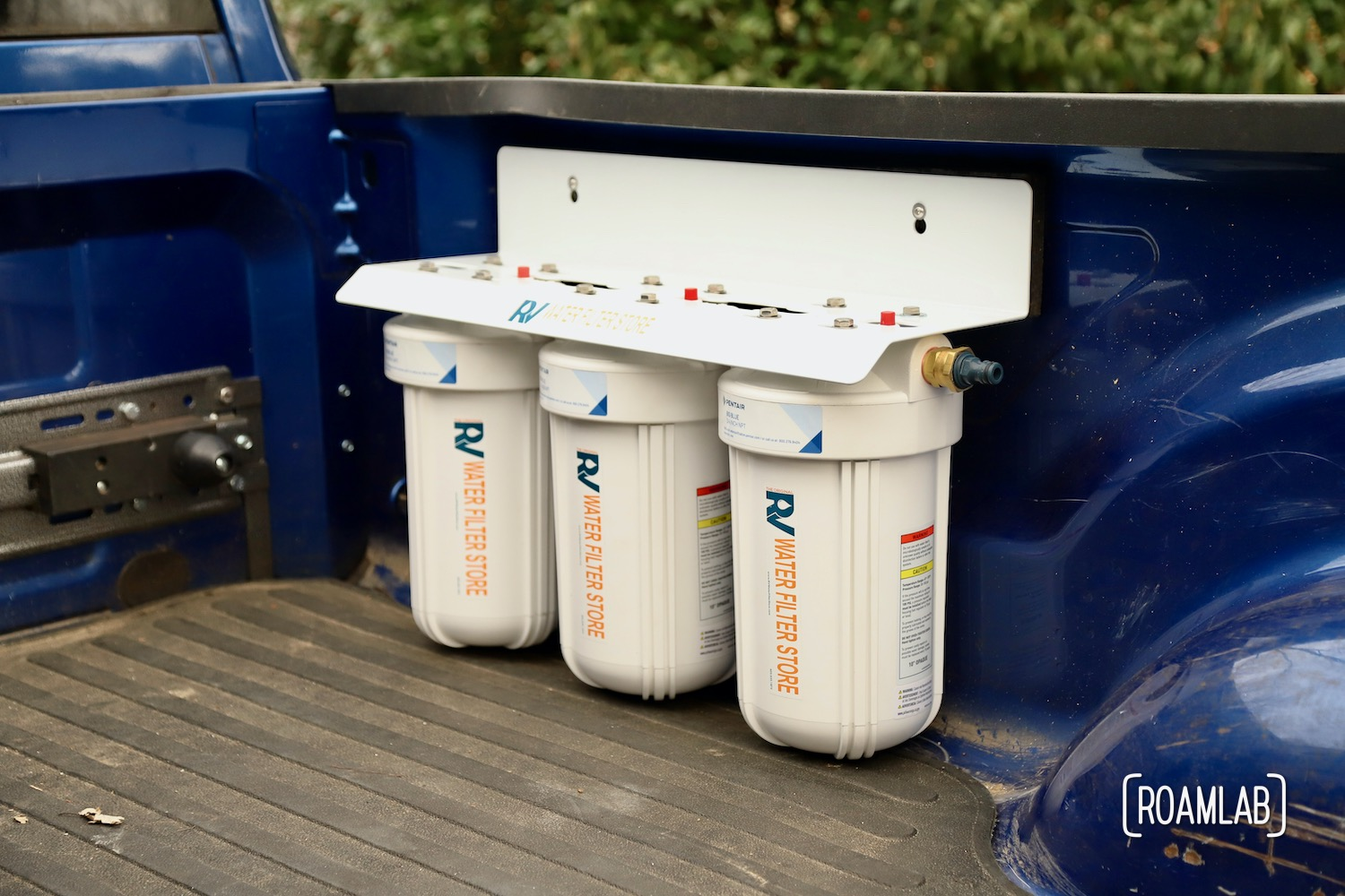 Large three canister water filtration system mounted to the passenger side of a truck bed.