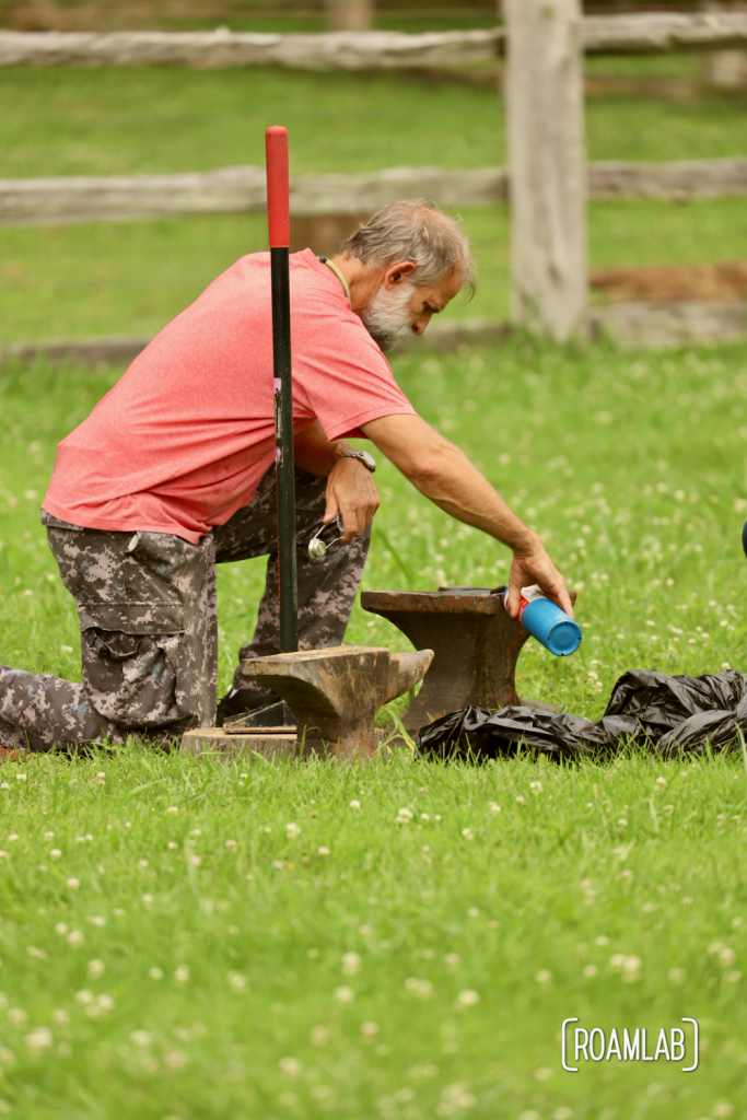 Man pouring black powder on an anvil in preparation of an anvil shoot.