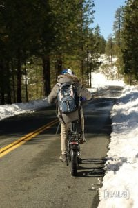 Man with a blue backpack riding a bike down a paved road with snow on each side in Foresthill OHV Trail System.