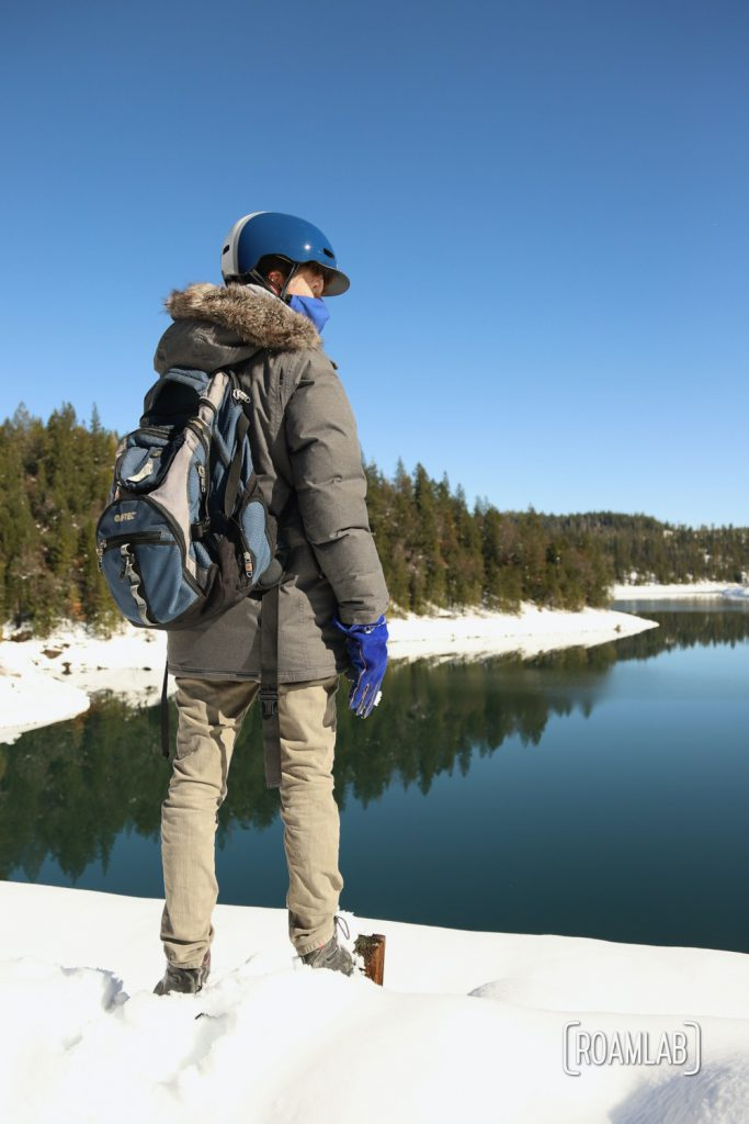 Man standing in show in front of the Sugar Pine Reservoir .