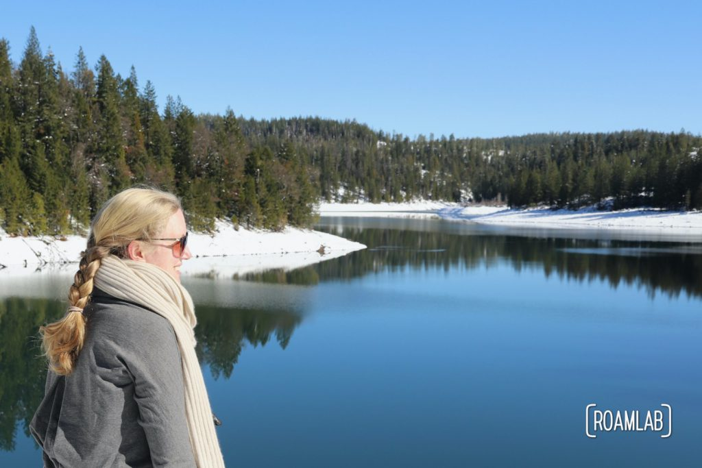 Woman looking out over the snowy shores of Sugar Pine Reservoir.