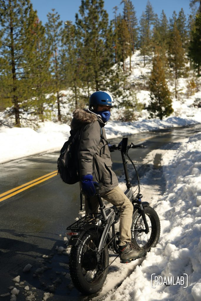 Man on a bike on the side of a road flanked by thick snow and pine trees in the Foresthill OHV Trail System