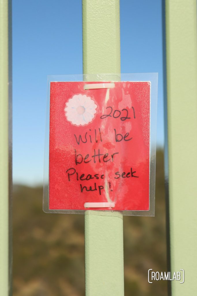 """Laminated message tied to Foresthill Bridge: """"2021 will be better. Please seek help!"""""""